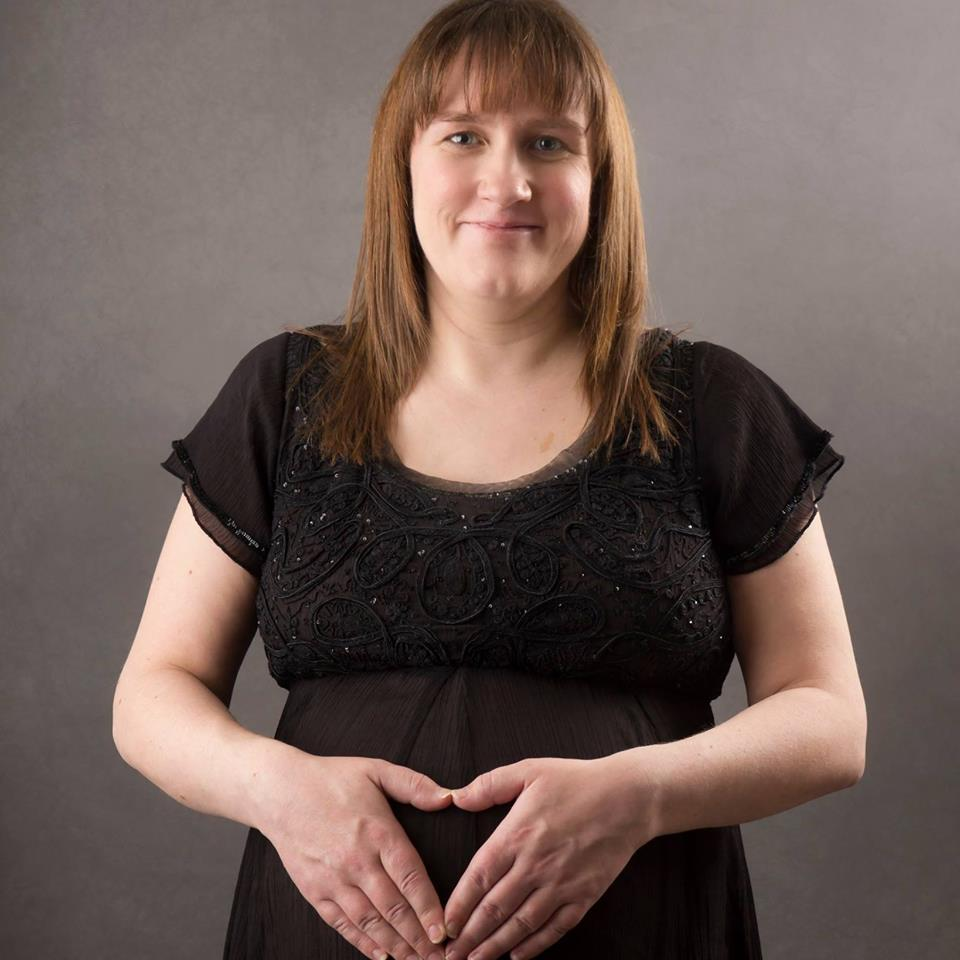 Heavily pregnant woman in her late 30s, with hands placed in heart shape in front of her bump