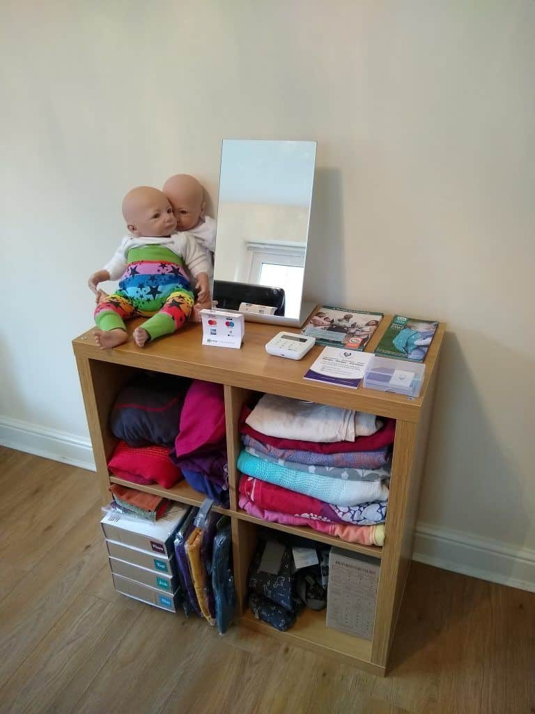 Display of slings, wraps and carriers suitable for newborn babies, along with a mirror and 2 newborn demonstrations dolls